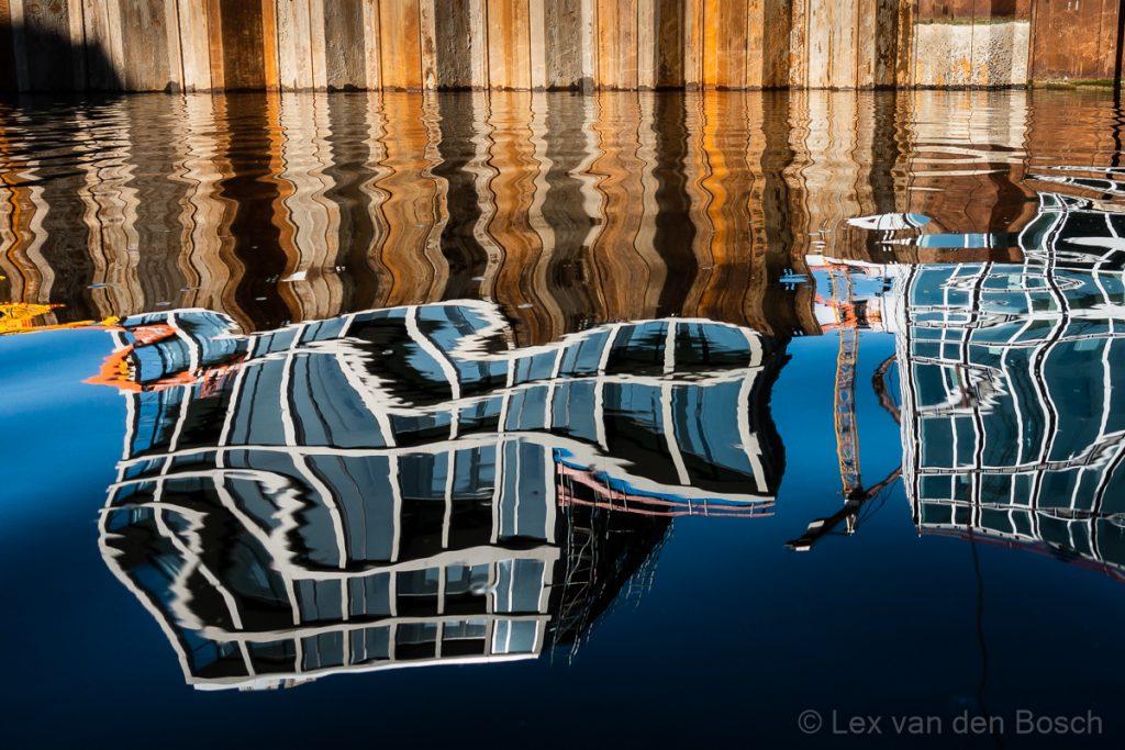 Een spiegeling in het water van nieuwbouw gefotografeerd vanuit de kajak in het centrum van Amsterdam
