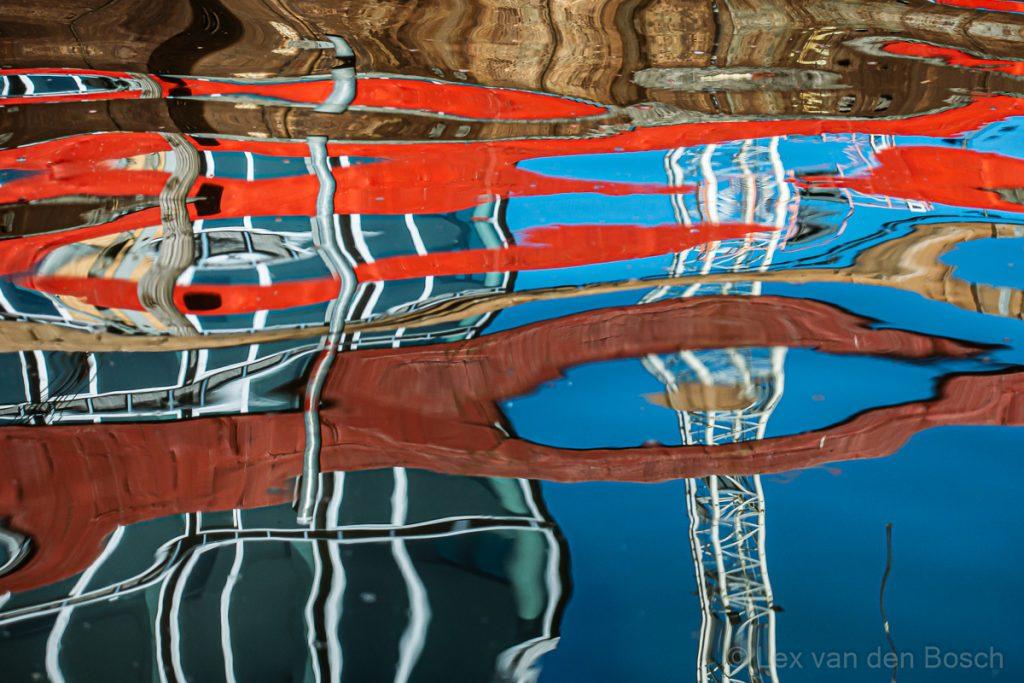 Een spiegeling in het water van gebouewen gefotografeerd vanuit de kajak in het centrum van Amsterdam