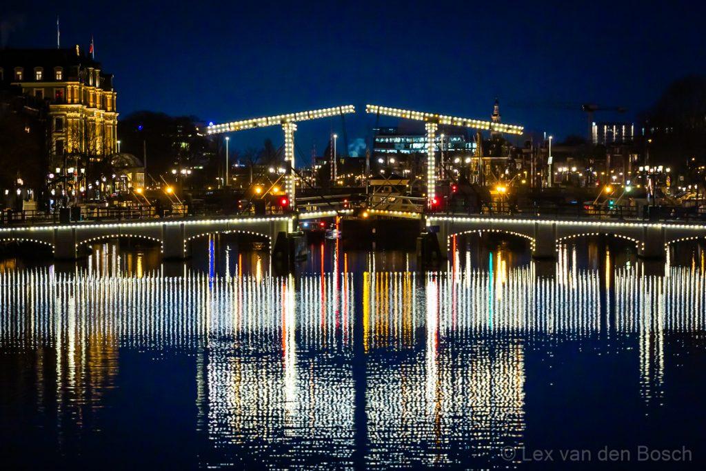 Spiegelingen in het water van de Amstel van een verlichte brug