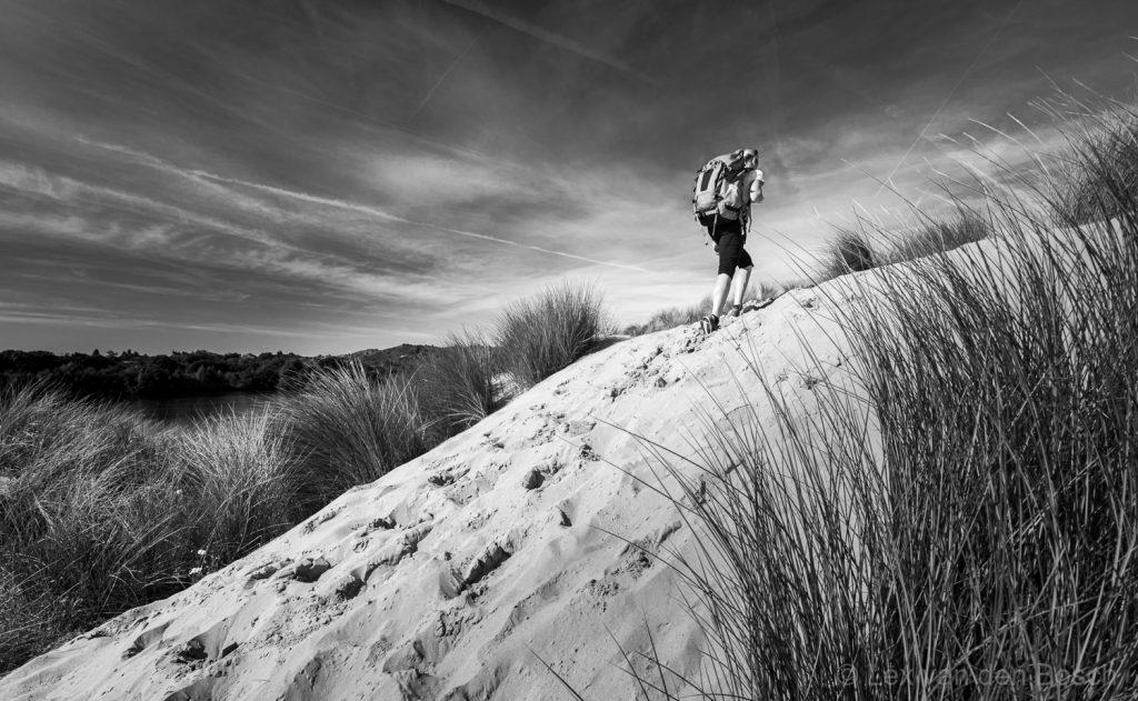 Door het zand omhoog met de rugzak tijdens een dagje wandelen in de Kennemerduinen