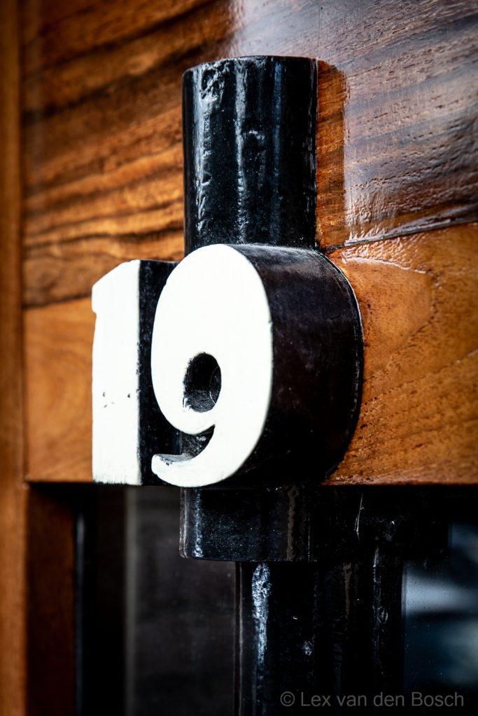 Huisnummer op deur met typografie die kenmerkend is voor de stijl van de Amsterdamse School