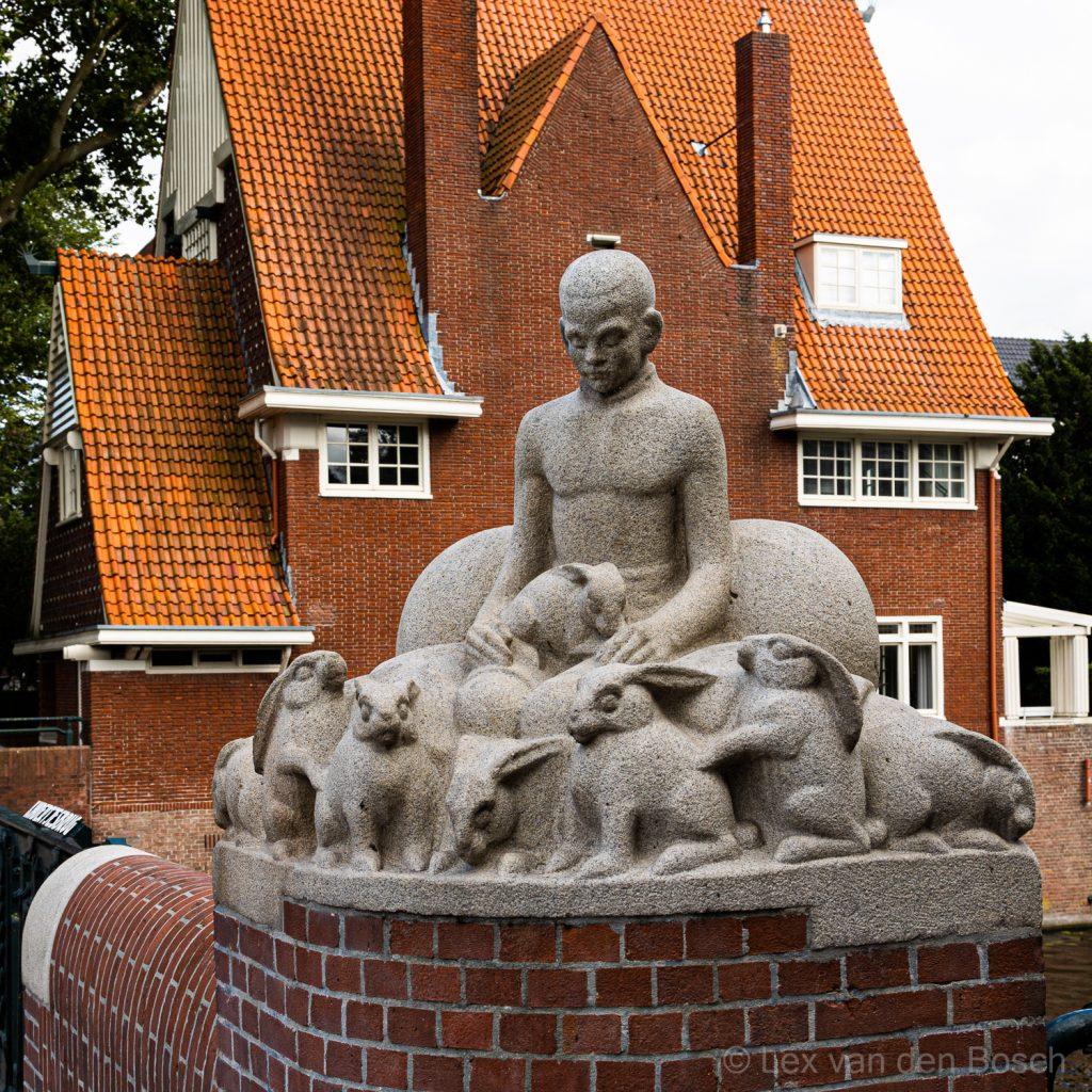 Beeld in Amsterdam-Zuid op brug met op de achtergrond een gebouw in Amsterdamse School stijl